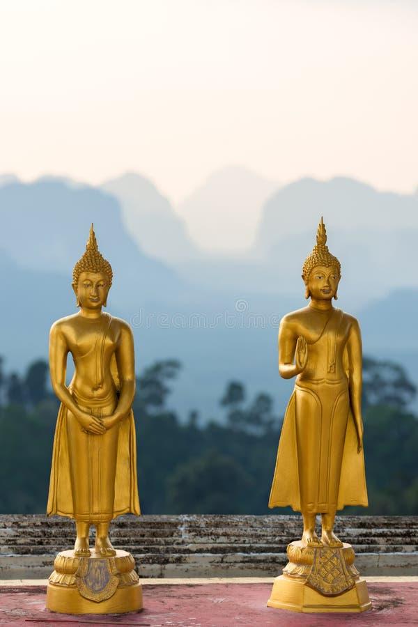 Небольшие статуи Будды в виске пещеры тигра Wat Tham Suea на предпосылке силуэтов гор внутри стоковое изображение rf