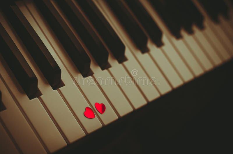 2 небольших красных сердца на клавиатуре классического конца рояля вверх Концепция любов и романтичной музыки стоковое фото