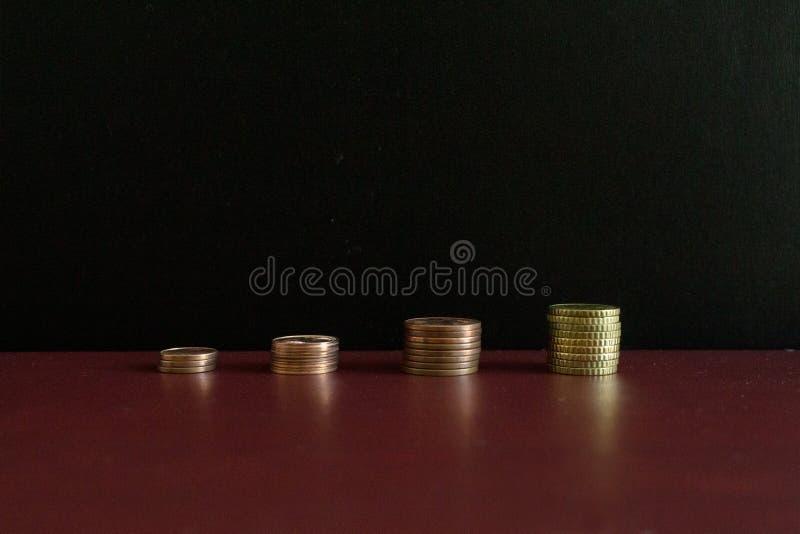 4 небольших стога монеток евро денег в ряд стоковые фотографии rf