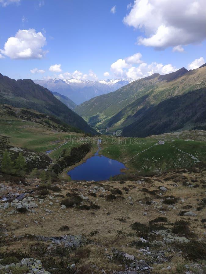 Небольшое высокогорное озеро с большими облаками и зеленой долиной стоковое фото