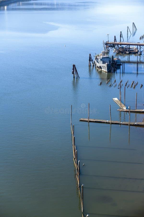 Небольшой буксир причаленный на старой пристани на реке стоковые изображения rf