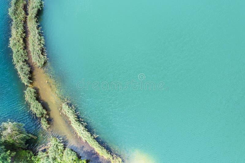 Небольшой вертел с путем покрытым с зеленой травой на обеих сторонах, на ясном озере Воздушное фотографирование стоковые изображения