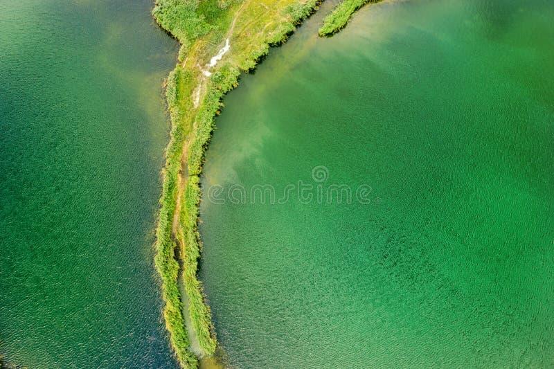 Небольшой вертел с путем покрытым с зеленой травой на обеих сторонах, на ясном озере Воздушное фотографирование стоковая фотография