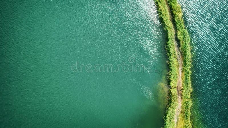 Небольшой вертел с путем покрытым с зеленой травой на обеих сторонах, на ясном озере Воздушное фотографирование стоковое фото