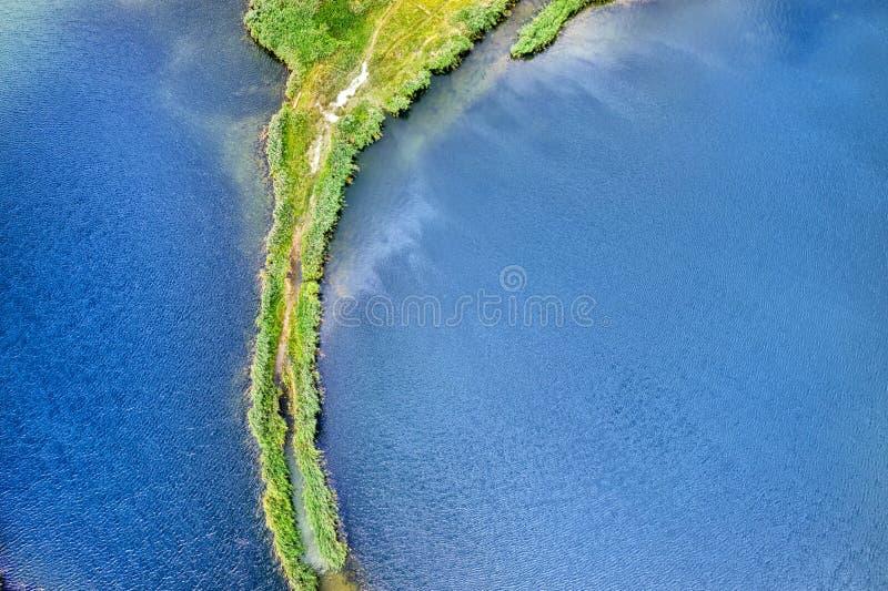 Небольшой вертел с путем покрытым с зеленой травой на обеих сторонах, на ясном озере Воздушное фотографирование стоковое фото rf