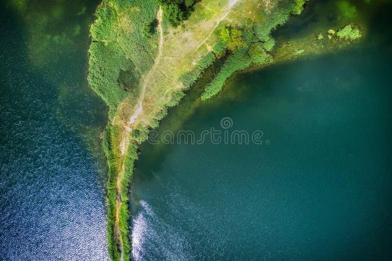 Небольшой вертел с путем покрытым с зеленой травой на обеих сторонах, на ясном озере Воздушное фотографирование стоковые фотографии rf