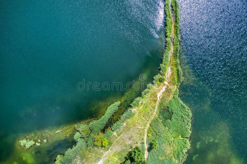 Небольшой вертел с путем покрытым с зеленой травой на обеих сторонах, на ясном озере Воздушное фотографирование стоковое изображение