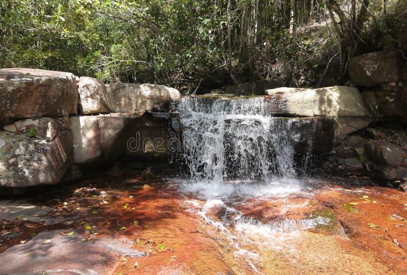 Небольшой водопад над оранжевыми камнями стоковые фото