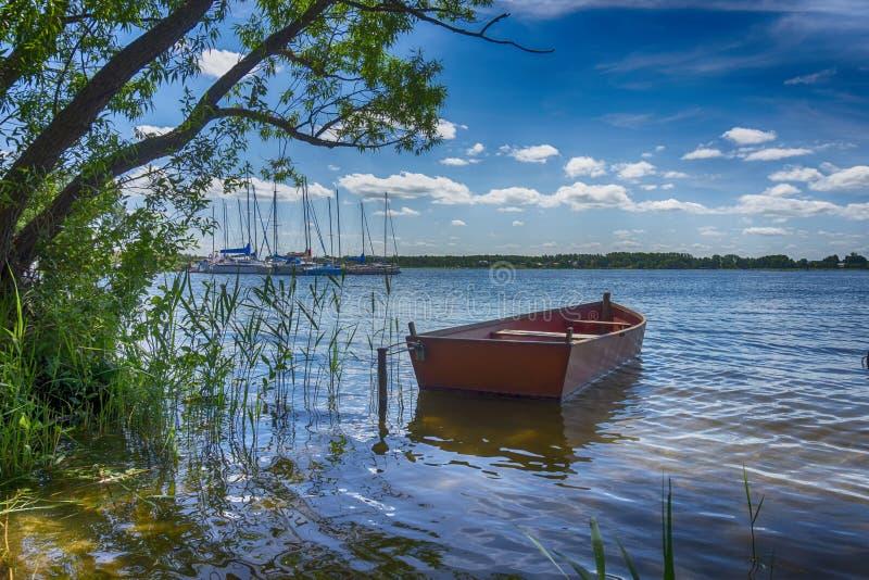 Небольшой деревянный rowboat причаленный на озере стоковое изображение rf