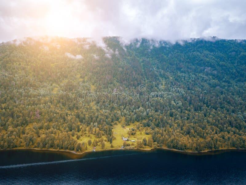 Небольшой дом в горах Altai около озера окруженного зелеными деревьями на солнечный день бабьего лета стоковые фото