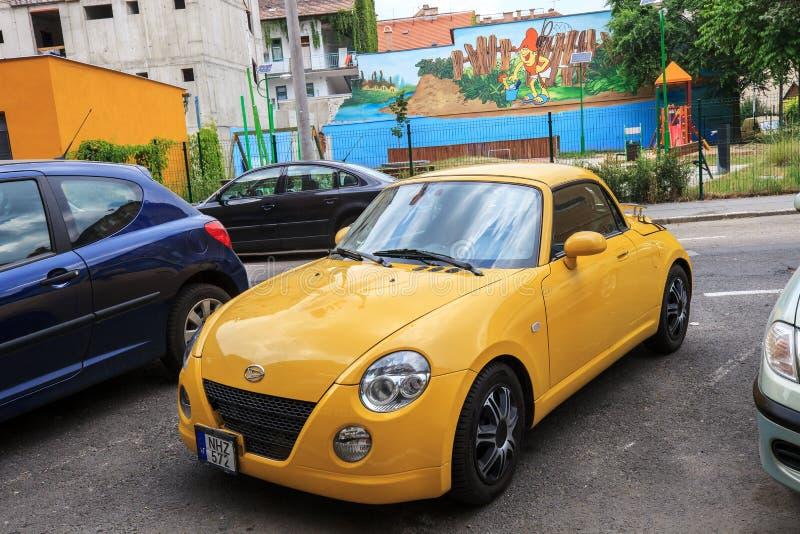 Небольшой желтый автомобиль Daihatsu Copen на улице города стоковое фото rf