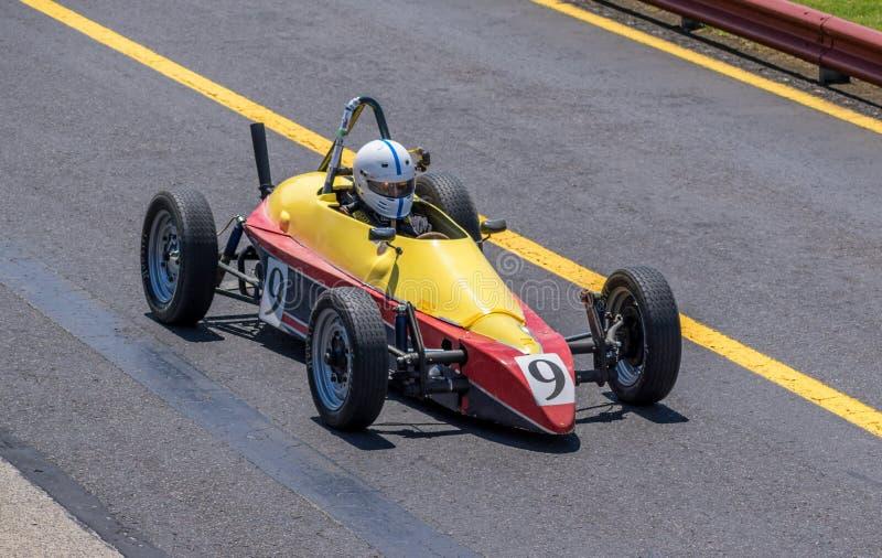 Небольшой желтый и красный винтажный гоночный автомобиль стоковые фото