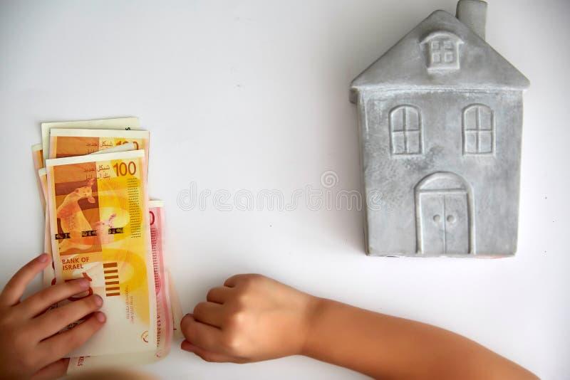 Небольшой каменный дом, рука ребенка переучитывает израильские шекели на белой предпосылке стоковая фотография rf