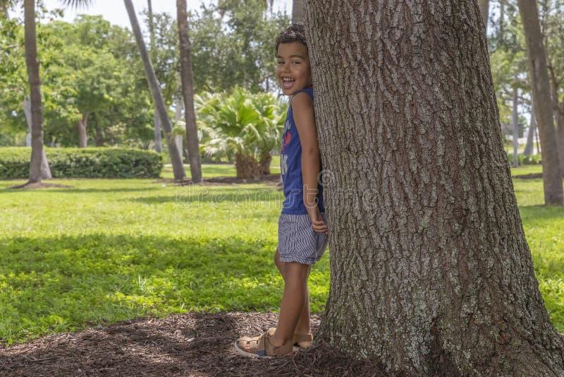 Небольшой мальчик полагается с его назад на большом дереве смеясь вне громко стоковое фото