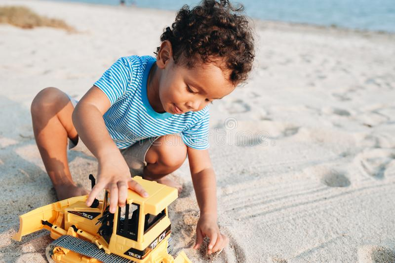 Небольшой мальчик смешанной гонки играя с игрушкой на пляже стоковые изображения rf