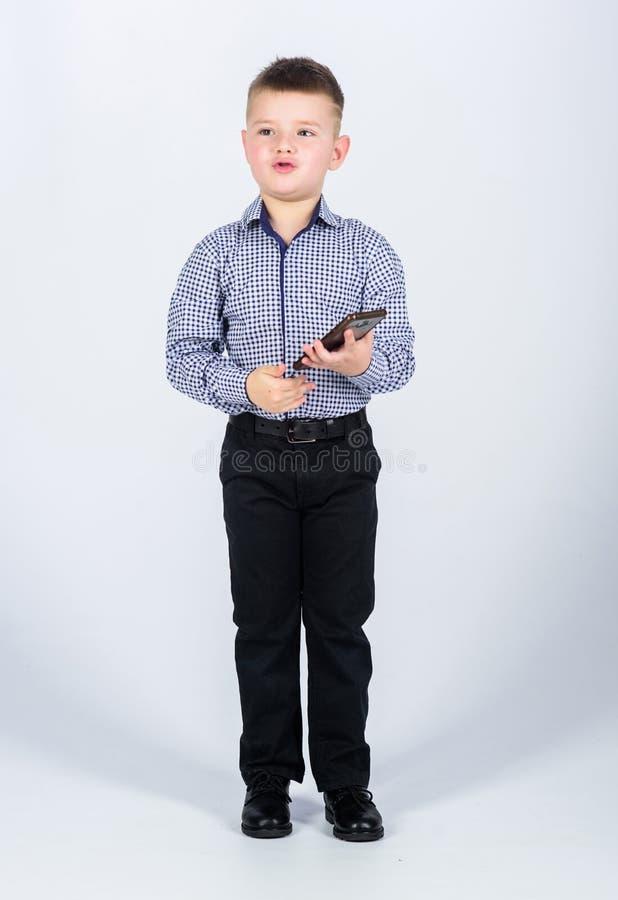 небольшой мальчик с мобильным телефоном маленький босс Direstor CEO (главный исполнительный директор) o r уверенный ребенок имеет стоковое изображение