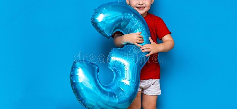 Небольшой милый белокурый мальчик на голубой предпосылке держа фольг-покрытый цвет baloon сферы голубой с днем рождения 3 лет ста иллюстрация штока