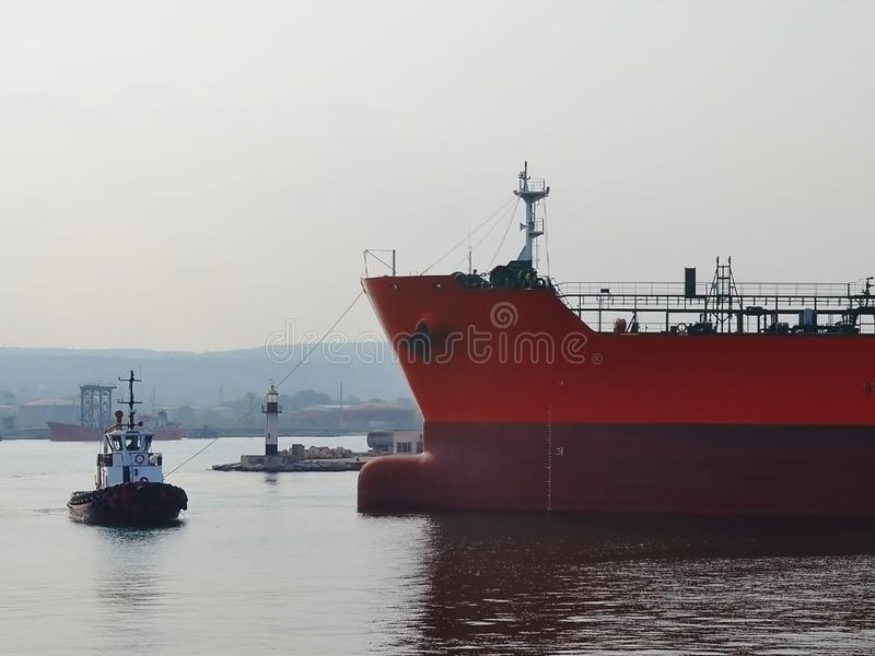 Небольшой пилотный корабль водит большой красный грузовой корабль на морском порте на windless день осени стоковые изображения