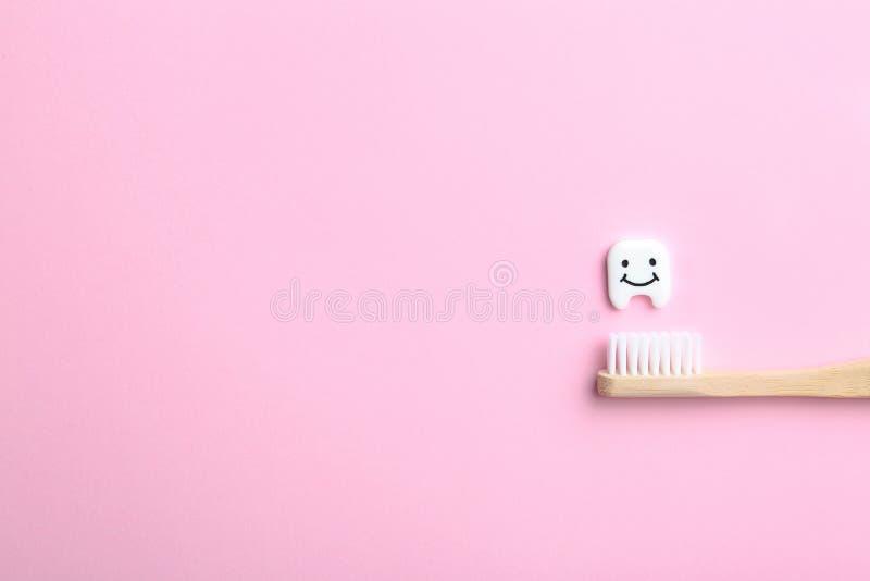 Небольшой пластиковый зуб, деревянная щетка и космос для текста на предпосылке цвета стоковые фотографии rf