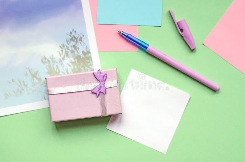Небольшой подарок бледной сирени Офис, стикеры на зеленой предпосылке стоковое фото rf