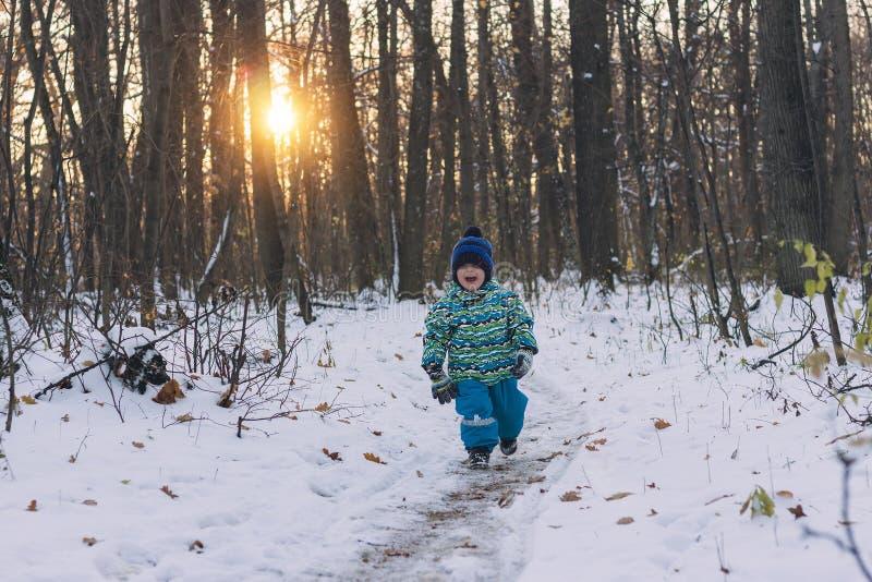 Небольшой ребенок идя на снежный путь среди хмурого леса стоковые фотографии rf