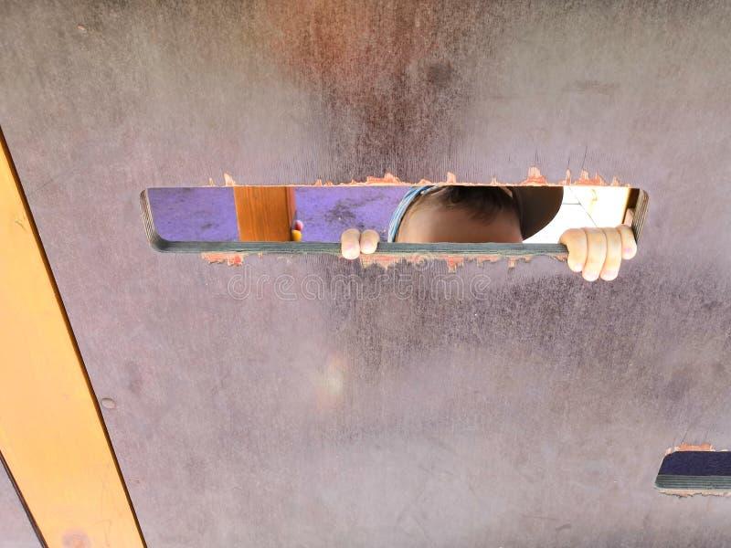 Небольшой ребенок смотря вне зазор коробки ремесла стоковое фото rf