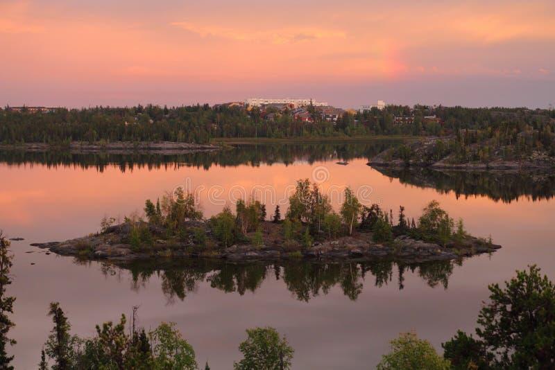 Небольшой скалистый остров в озере рамк в драматическом выравниваясь свете, Йеллоунайф, северо-западных территориях стоковое фото rf