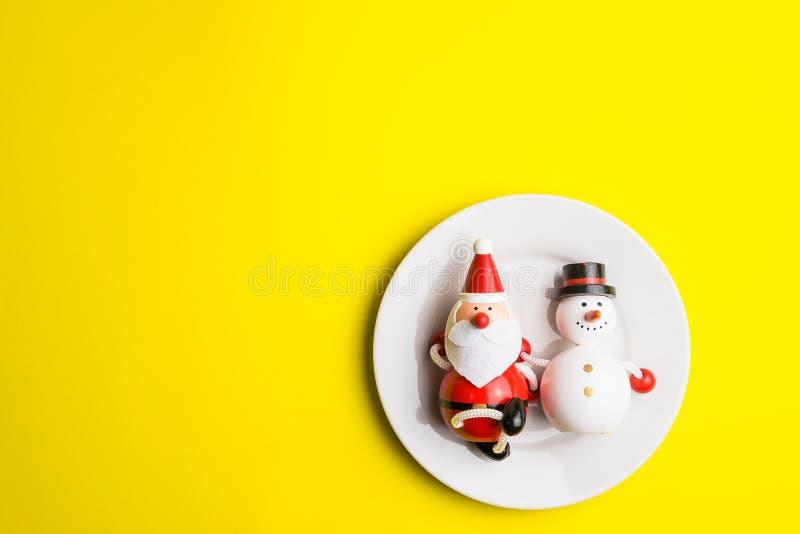 Небольшой снеговик и небольшой Санта Клаус на белом блюде на ye стоковая фотография