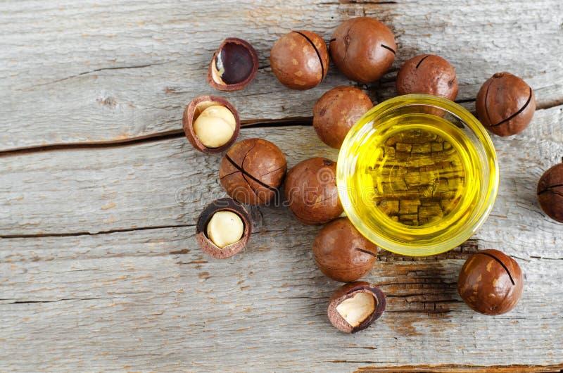 Небольшой стеклянный шар с ореховым маслом макадамии и гайками макадамии над старой деревянной предпосылкой стоковое изображение rf