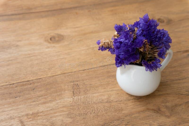 Небольшой фиолетовый цветок в белой чашке на деревянном столе стоковое фото rf