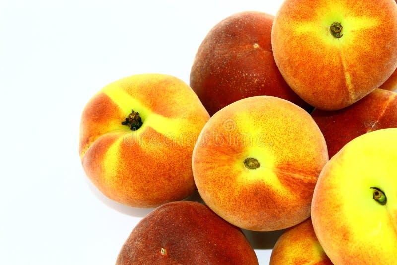 Небольшой холм красных и желтых персиков на белой предпосылке стоковые фотографии rf