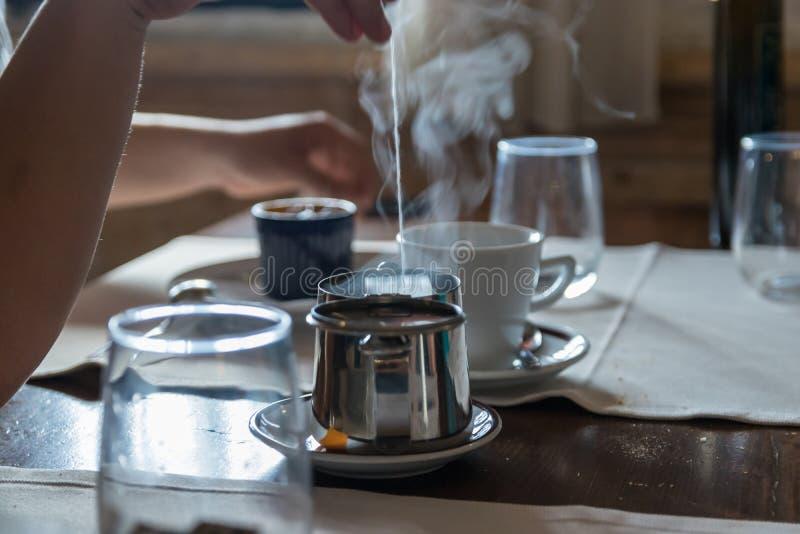 Небольшой чайник с пакетиком чая, некоторые стекла металла на таблице ресторана Белый пар поднимает над горячей водой r стоковая фотография rf