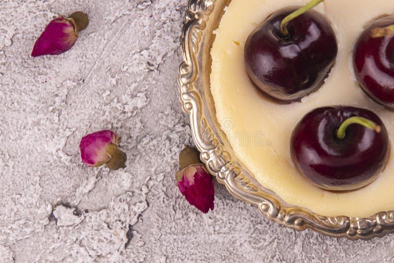 Небольшой чизкейк части со свежими сладкими вишнями против серой предпосылки стоковая фотография rf