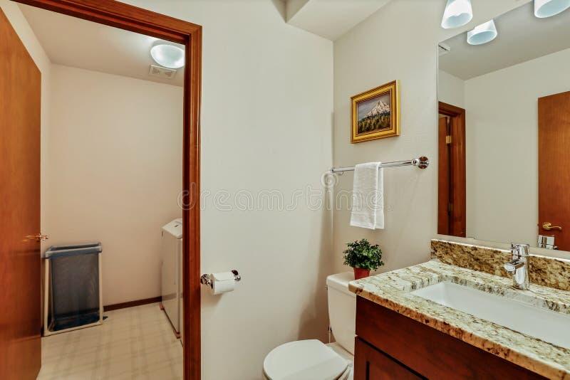 Небольшой Bathroom гостя с деревянными тщетой и открыть дверью стоковая фотография rf