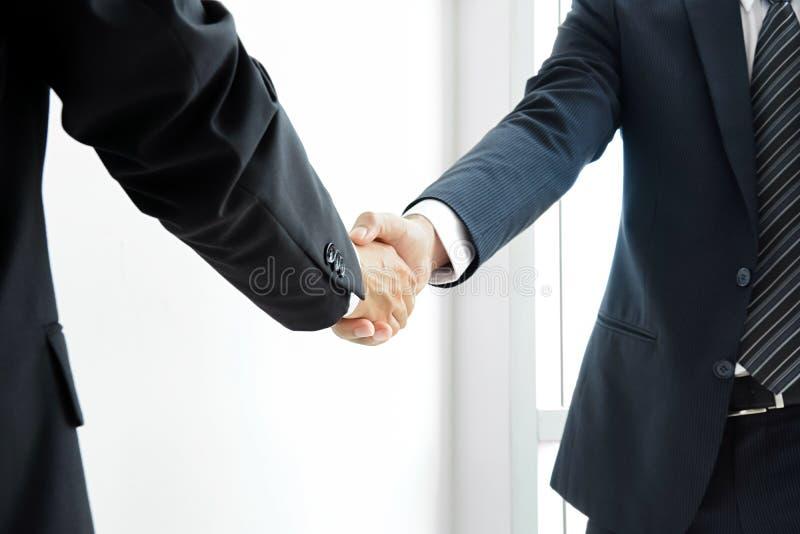 небо бизнесменов предпосылки изолированное рукопожатием стоковая фотография