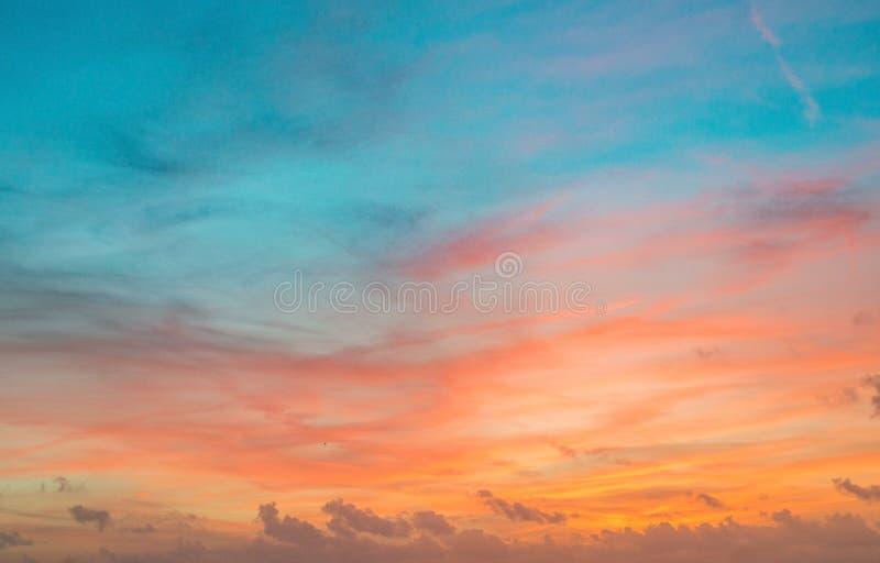 Небо захода солнца в красном и голубом цвете с тонкими облаками стоковое фото