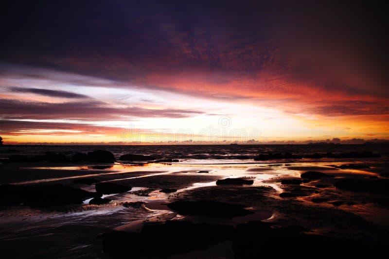 Небо с глубокими вися облаками шторма и влажной шугой во время малой воды swathed в желтом и красном ярком свете во время захода  стоковое изображение