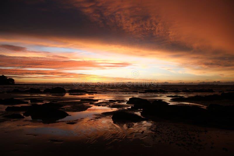 Небо с глубокими вися облаками шторма и влажной шугой во время малой воды swathed в желтом и красном ярком свете во время захода  стоковая фотография rf