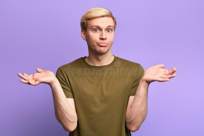 Невежественный и озадаченный молодой красивый человек смущая выражение стоковое фото rf