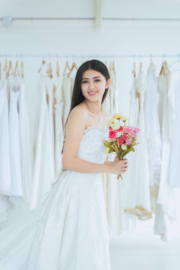 Невеста в белом платье держа букет в наличии на свадьба, момент красивой азиатской женщины усмехаясь и счастливый, романтичный и  стоковые фото