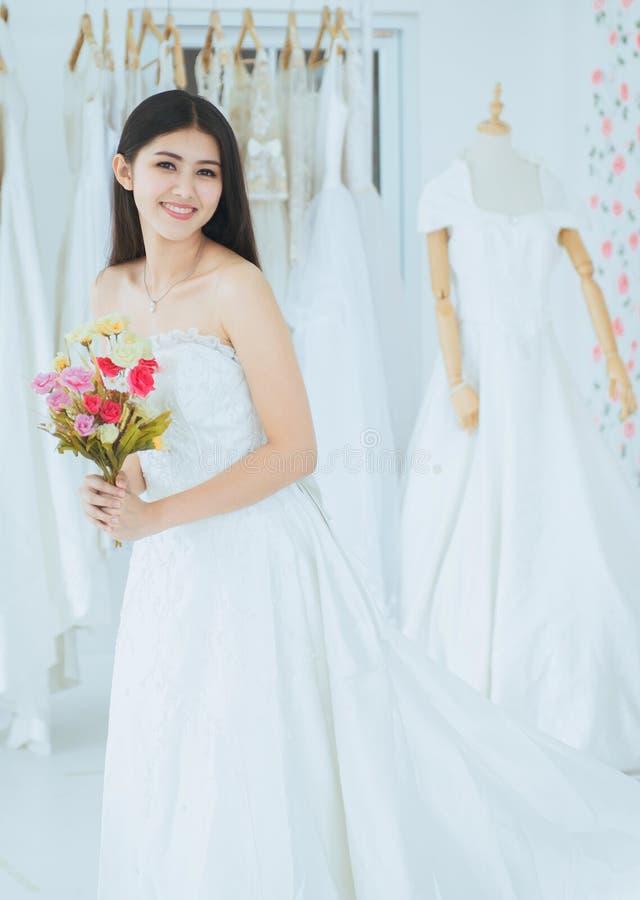 Невеста в белом платье держа букет в наличии на свадьба, момент красивой азиатской женщины усмехаясь и счастливый, романтичный и  стоковая фотография rf