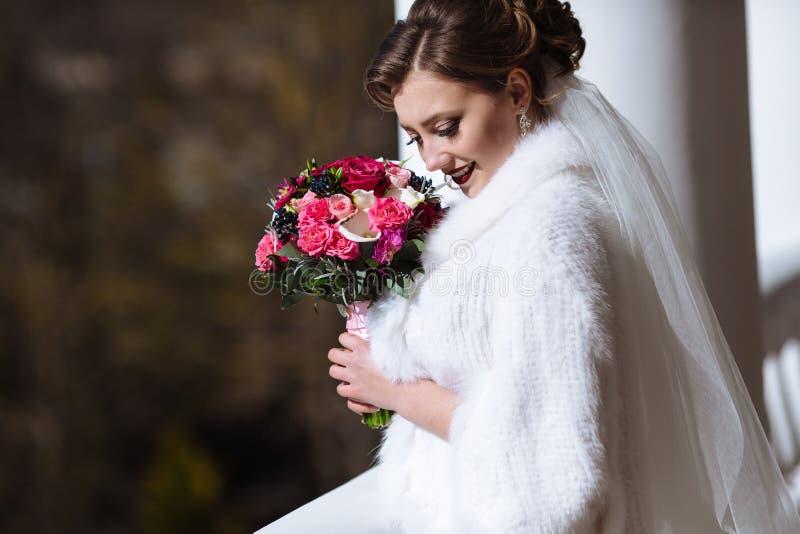 Невеста в белом смехе одежд и имеет потеху на улице Портрет маленькой девочки с букетом, она понизила ее стоковое фото rf