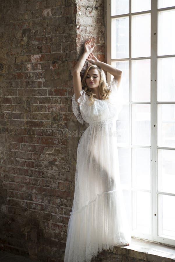 Невеста в красивом белом платье представляя против окна стоковое изображение rf