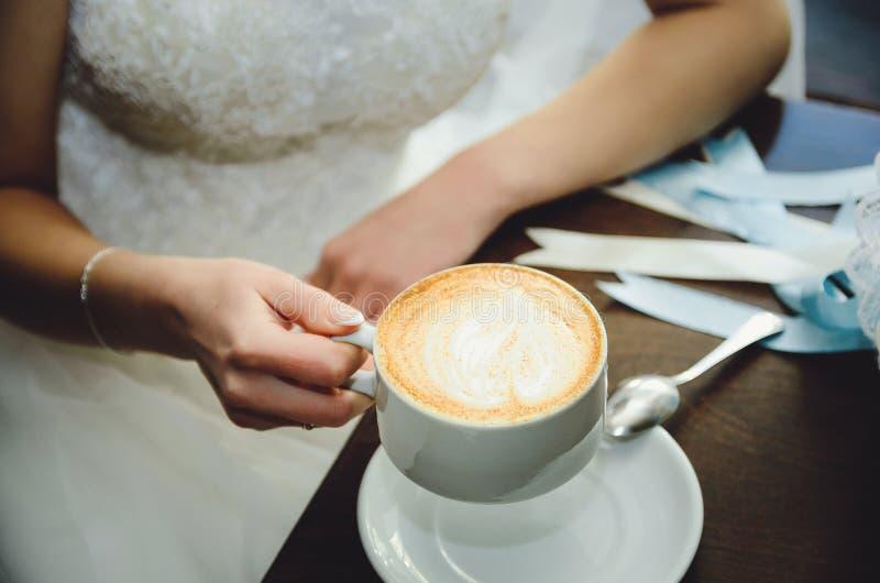 Невеста в платье свадьбы выпивает кофе в кафе стоковая фотография
