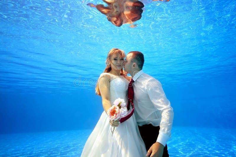 Невеста в платье свадьбы обнимая underwater groom в бассейне держа цветки в ее руке и смотря камеру стоковое фото