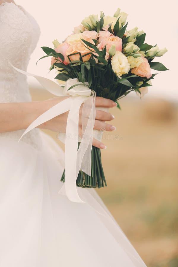 Невеста в элегантном платье свадьбы держит красивый букет различных цветков и зеленых листьев Тема свадьбы стоковые фото