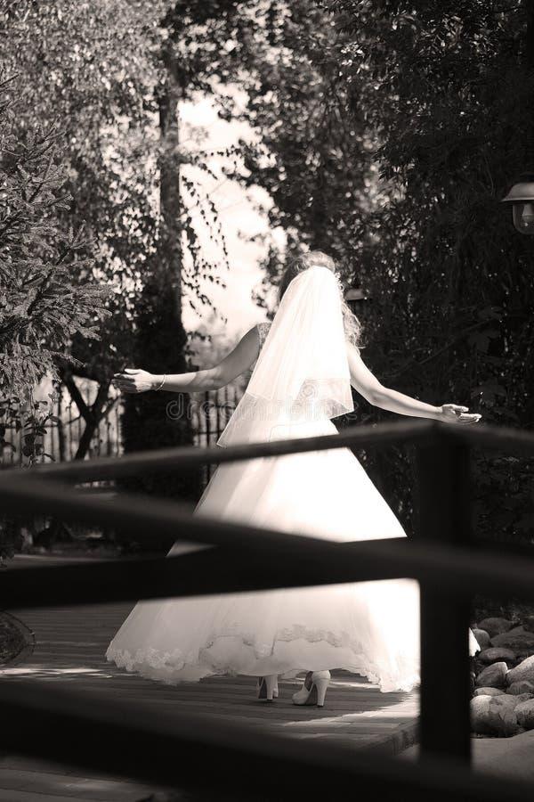Невеста делая пируэт в парке стоковая фотография rf