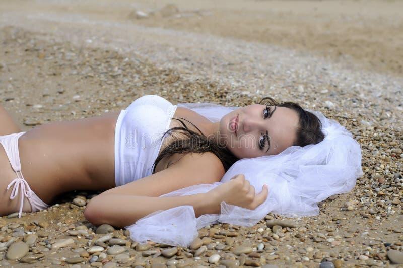 Невеста лежа на пляже стоковое фото