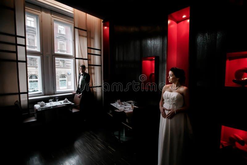Невеста лежит ее руки на животе стоя в клетке и восхищаясь стоковая фотография