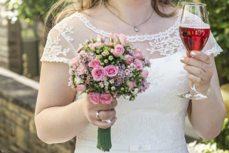 Невеста держа букет цветков и замужества свадьбы крупного плана бокала вина стоковые изображения